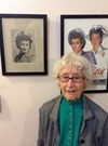 Photo of Lois Ross in front of two USCNC photos